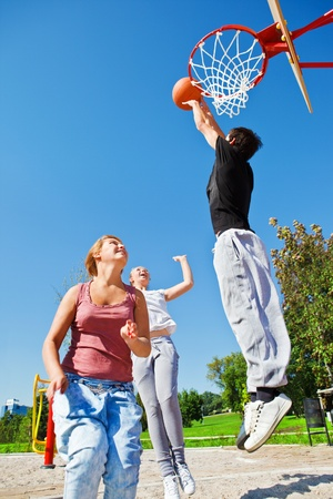 Teenagers playing basketball in a city park photo