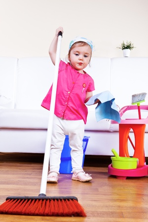 Lovely toddler girl cleaning the room