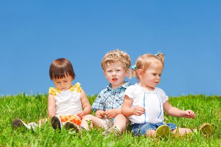 Babies sit on grass against blue sky photo