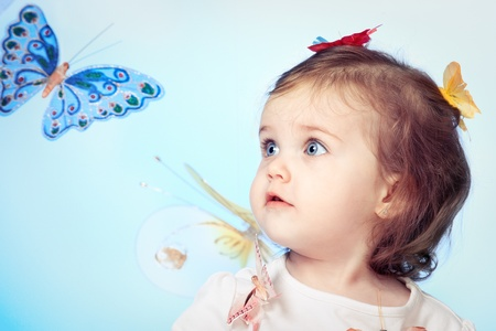 Portrait of sweet little girl, with butterflies in the background