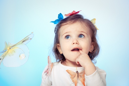 Angelic baby girl looking puzzled, over blue photo