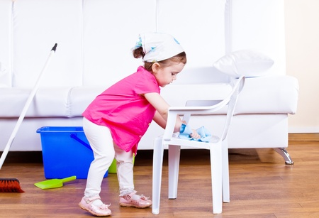 Little girl wiping  dust off a kid chair
