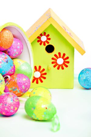 Easter eggs lying in container with bird house in the background Stock Photo - 12973096