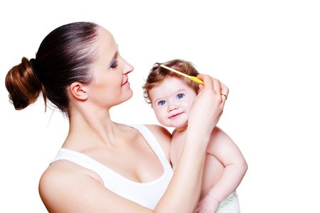 Loving mother combing baby hair photo