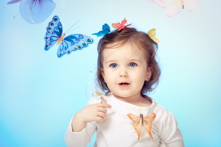 Laughing little girl with butterflies all around photo