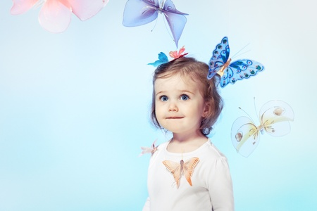 Happy toddler girl over blue background photo
