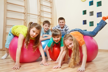 kid sitting: Five kids playing with gymnastic balls