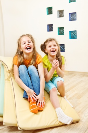 Laughing little girls sit on tumbling mats photo