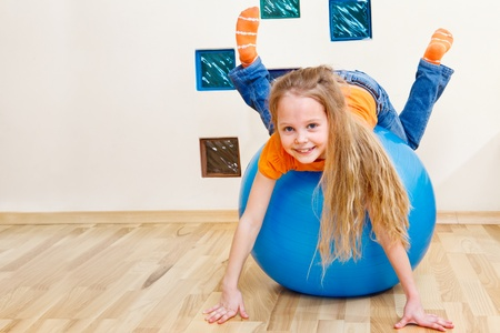 sitting small: Cheerful little girl playing with gymnastic ball