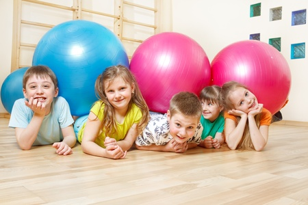 group of colourful ball: Five happy kids lie in gym with large balls Stock Photo