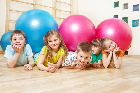 Vijf gelukkige kinderen liggen in de gymzaal met grote ballen