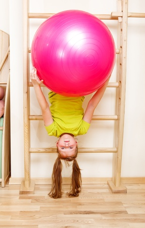 wall bars: Elementary aged girl hanging on wooden wall bars with a large gymnastic ball Stock Photo