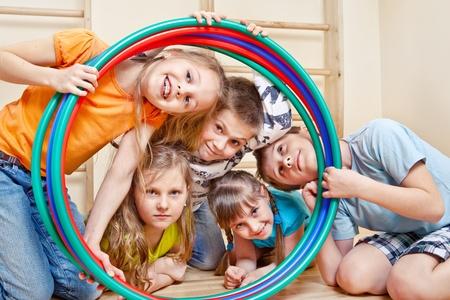 Portrait of laughing children looking through hula hoops Foto de archivo