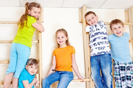 Active children climbing up the gymnastic wall bars Foto de archivo