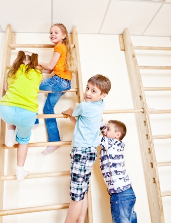 wall bars: Active friends climbing up the wall bars in gym Stock Photo