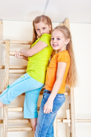Happy little girls climbing wall bars Stock Photo - 13138877