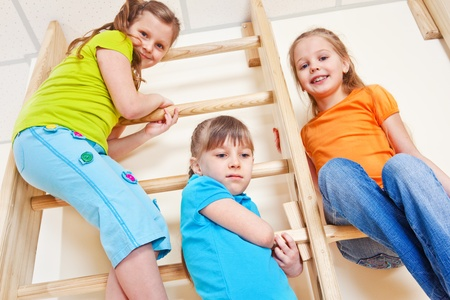 Three kids in bright clothing up high on the wall bars Stock Photo - 13138898