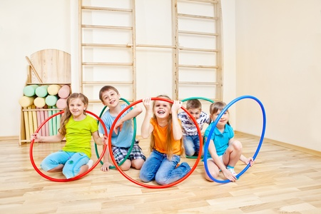 Children group playing with hula hoops photo