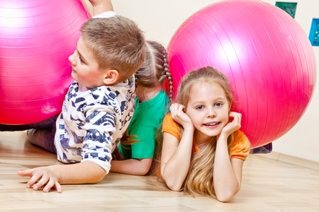 sportive: Cute children playing with large gymnastic balls