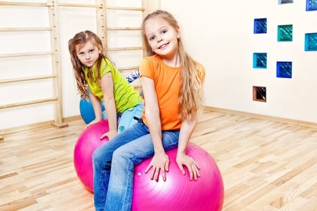 large ball: Smiling students sit on gymnastic balls Stock Photo