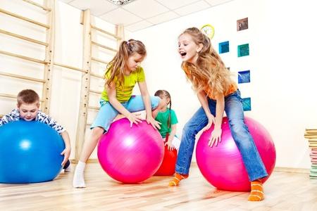 kid smiling: Active kids jump on gymnastic balls
