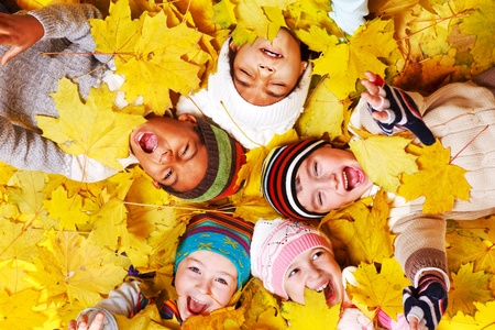 Autumnal screaming kids group in yellow leaves Foto de archivo