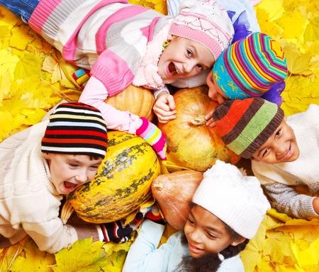 Emotional kids on yellow autumnal leaves Foto de archivo