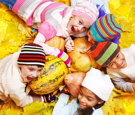 fall fun: Emotional kids on yellow autumnal leaves Stock Photo