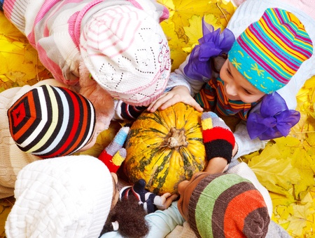 Kids in hats lie on leaves around pumpkin Stock Photo - 13191273