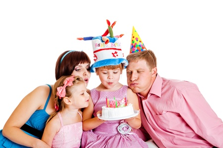Family blowing out candles on birthday cake photo