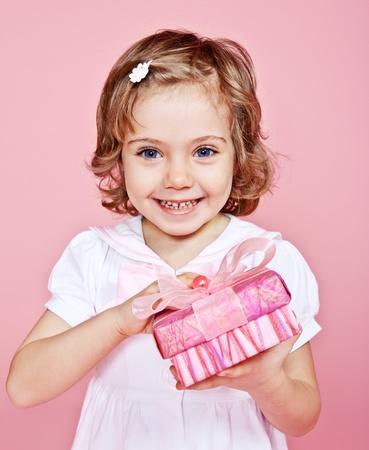 Pink present box in hands of a happy girl Foto de archivo