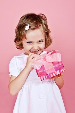Joyful little girl holding pink present in hands