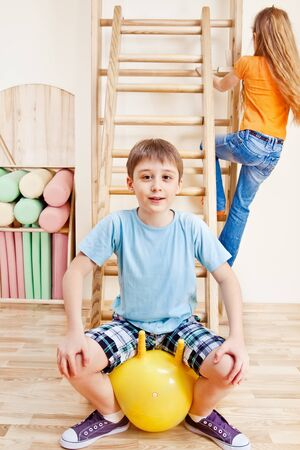Elementary aged boy sitting on yellow gymnastic ball photo
