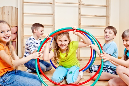 Happy children holding colorful hula hoops in gym photo