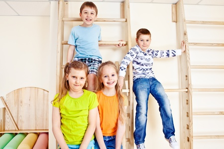 Little girls and boys sit on wall bars in gym Stock Photo - 13301081