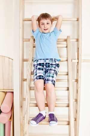 wall bars: Primary school student sit on wall bars Stock Photo