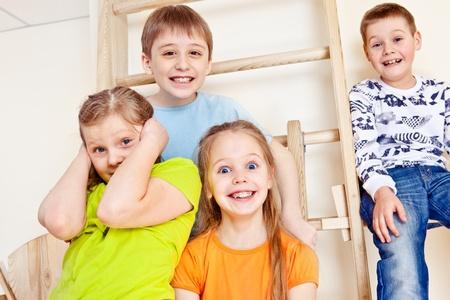 Joyful kids group sitting on wall bars Stock Photo - 13301049