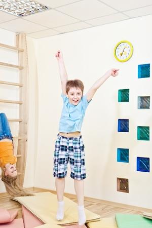 ni�o saltando: Ni�o feliz saltando en el gimnasio