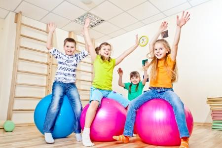 enfants qui jouent: Enfants �motionnels de sauter sur une balle de gymnastique Banque d'images