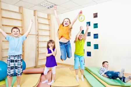 ni�os jugando en la escuela: Alegre grupo de salto de los estudiantes de escuelas primarias