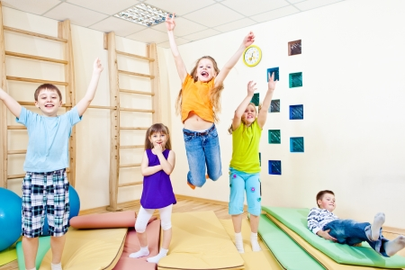 school gym: Cheerful jumping group of primary school students