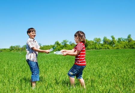 Happy kids spraying water in the outdoor photo