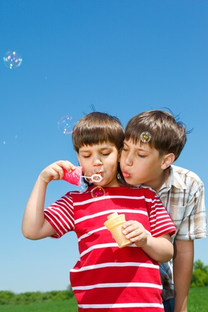 Boys blowing bubbles against blue sky photo