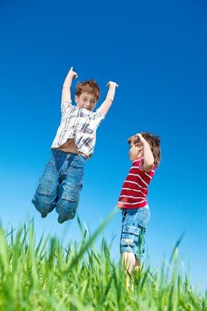 Happy Kids springen in het gras Stockfoto