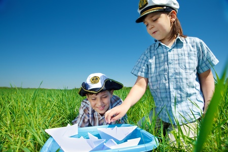Two boys in captain caps playing with paper boats photo