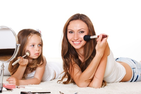 Daughter looks at mother applying makeup photo