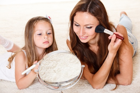 Young woman and little girl looking into mirror photo