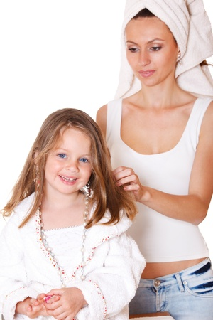 Smiling girl with beads and earring on, and her mother brushing hair photo
