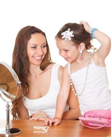 Cheerful girl looking to the mirror and her happy mother  Stock Photo