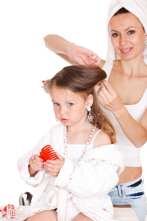 Young mother styling daughter's hair photo